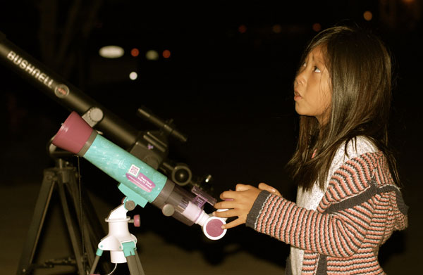 Addie looks through a telescope