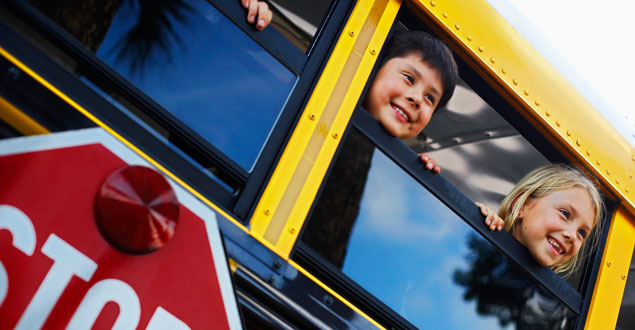 happy kids leaning out school bus windows