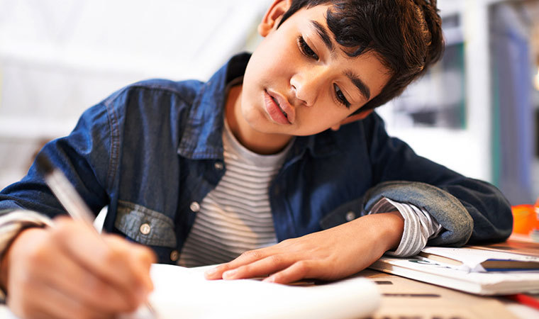 Young boy writing at a desk