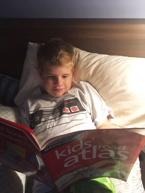 Young boy reading Rand McNally Kids' Road Atlas in bed