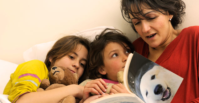 mother reading nonfiction book to her two children