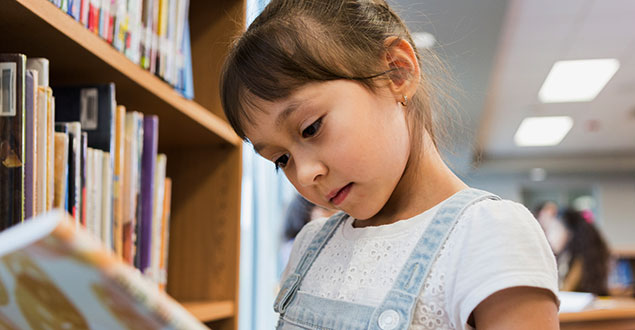 early elementary grade girl reading book in library