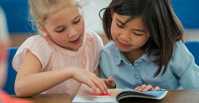 Two first grader girls reading decodable text