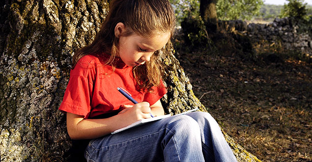 young girl outside writing in her journal