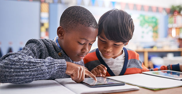 two elementary students working on tablet