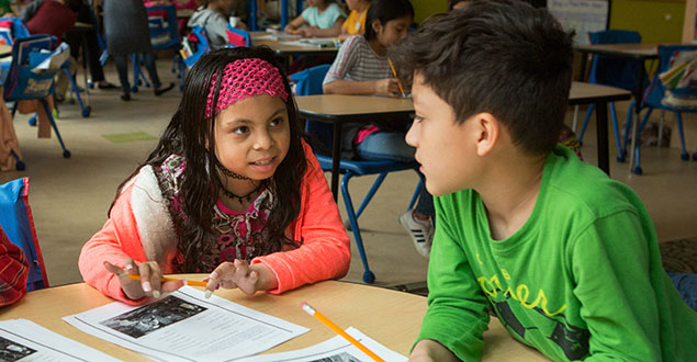 two English language learners in elementary classroom writing and talking