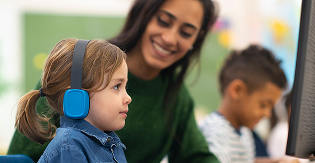 teacher guiding elementary student wearing headphones