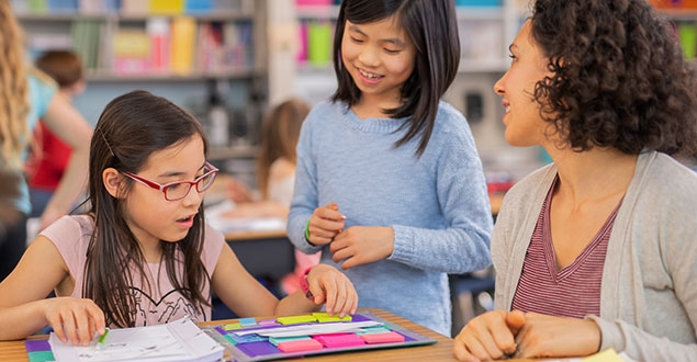 Two elementary students with teacher in inclusive classroom