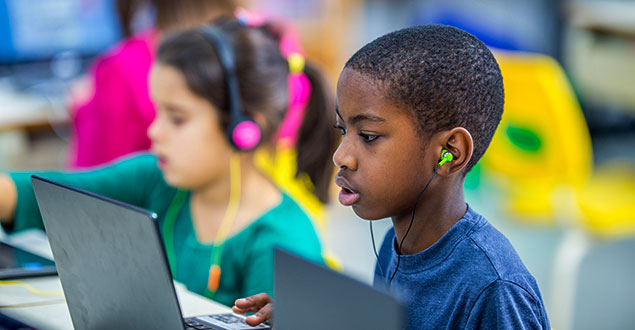 Elementary students using computers with headphones in classroom