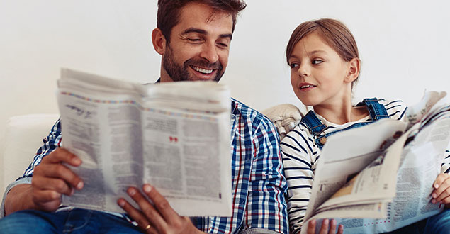 Father and daughter reading newspapers side-by-side