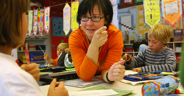 Reading instruction with teacher and her elementary students