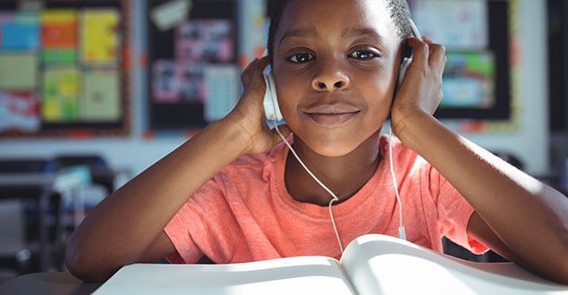 Young girl in classroom with headphones