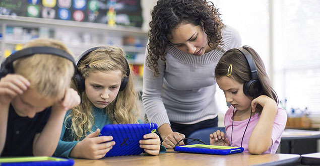 Teacher helping three students with reading using tablets