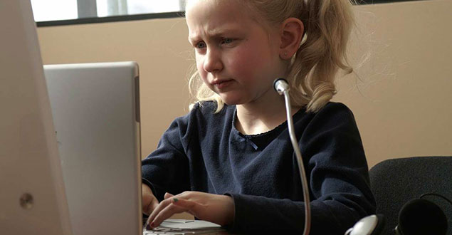 Young girl working at a desktop computer