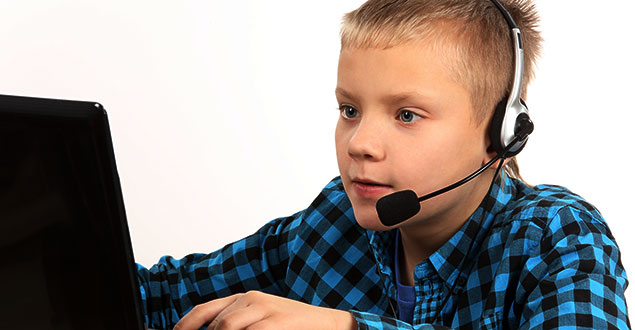 Elementary age boy using dictation technology on a computer