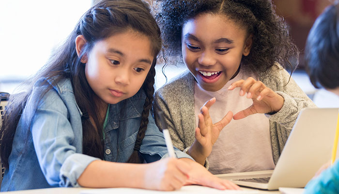 Asian girl and Black girl writing and discussing in elementary classroom