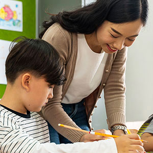 Asian elementary teacher working with Asian student in class