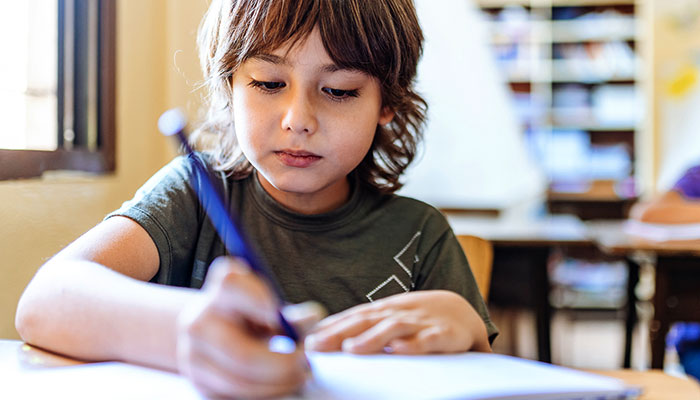 Elementary aged boy practicing writing and spelling
