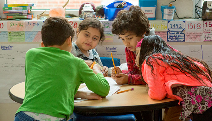 Four elementary aged kids working on vocabulary together
