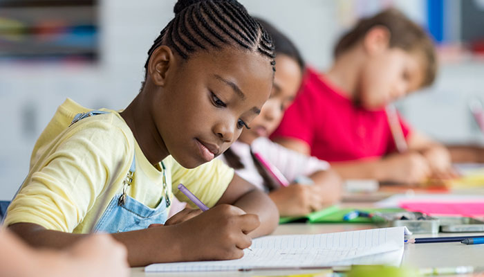 African American girl practicing writing with elementary aged classmates