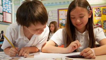 A young boy and girl look at a page on the desk and smile