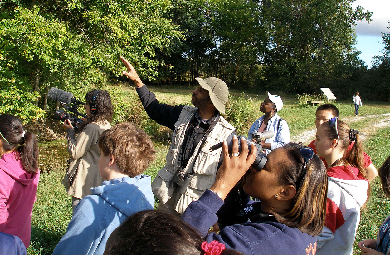 Ornithologist and wildlife biologist John C. Robinson outside leading a multicultural, multiage birding group