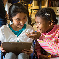 Two elementary students in classroom discussing their reading