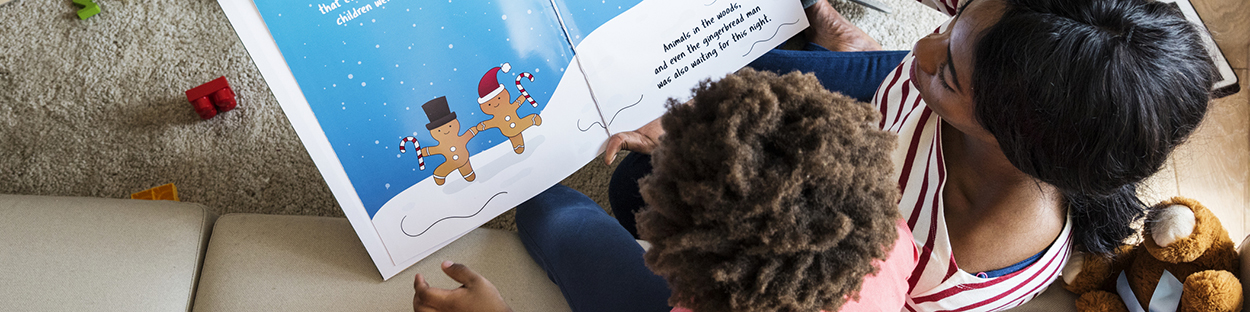 African American mother reading picture book to kindergarten son