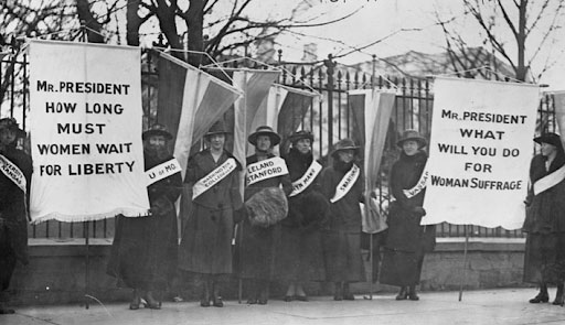 Suffragists out in the streets with banners
