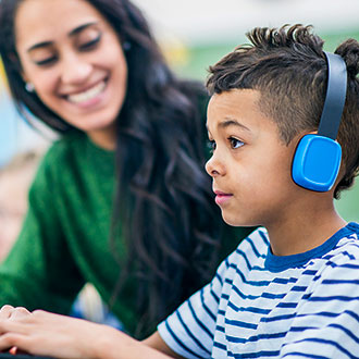 teacher and student, with student at computer wearing headphones
