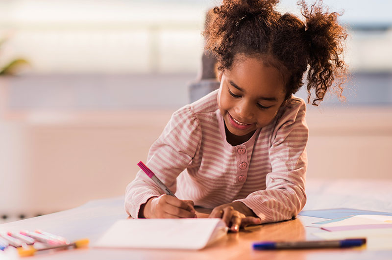 5 year old girl writing at her desk at home